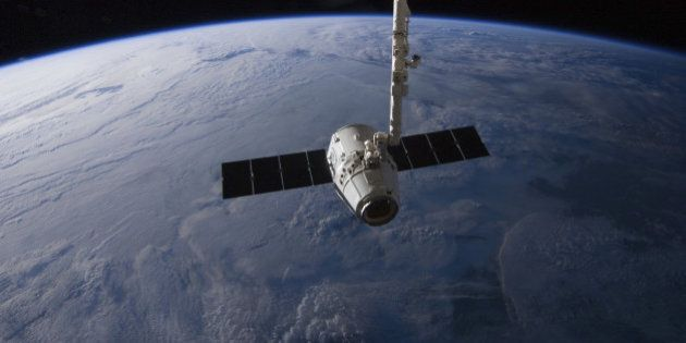 May 31, 2012 - The SpaceX Dragon cargo craft is suspended in the grasp of the Candarm2 robotic arm some...