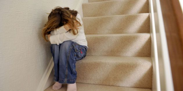 Young girl (6 years of age) sits on the landing of a staircase and covers her face. KEYWORDS: bullying,...