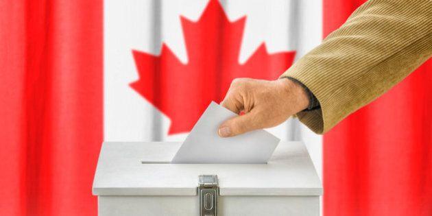 Man putting a ballot into a voting box - Canada
