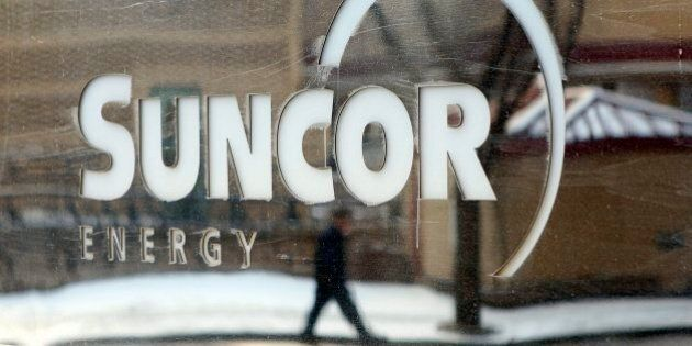 A pedestrian is reflected in a Suncor Energy sign in Calgary, Alberta, Monday, Feb. 1, 2010. The future...