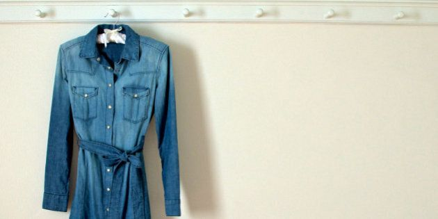 Weathered denim dress with pearl buttons hanging against plain white