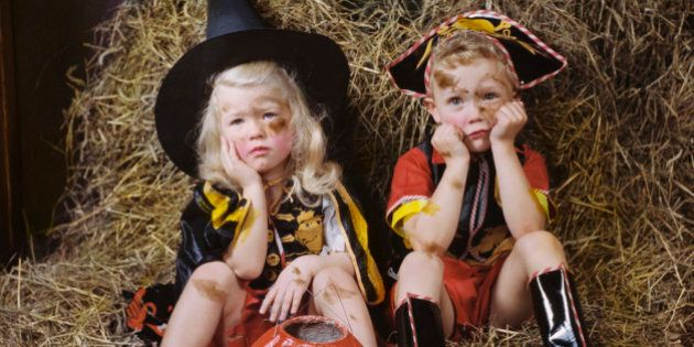 Children wearing costumes sitting on hay with sad faces
