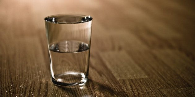 Half-filled glass of water on table.
