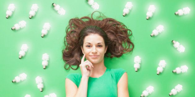 Girl laying on Green background with CF light bulbs around