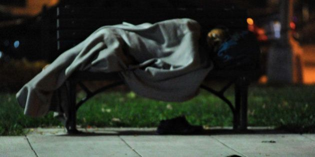 WASHINGTON, DC - AUG 08: A rat scurries along the sidewalk as a homeless person sleeps on a park bench...
