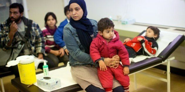 Members of a Syrian refugee family from Damascus wait to get vaccinations at the State Office of Health...