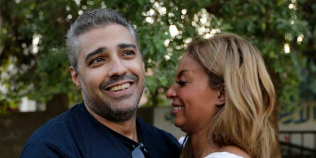 Canadian Al Jazeera English journalist Mohamed Fahmy hugs his wife Marwa Omara after being released from...