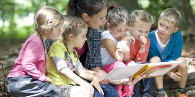 Kindergarten teacher reading with kids in a wood