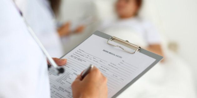 Female medicine doctor filling in patient medical history list during ward round. Medical care or insurance concept. Physician ready to examine patient and help