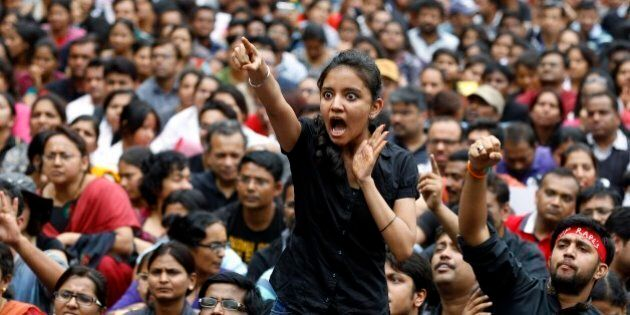An angry protester points her finger towards the Bangalore police chief during a protest against alleged...