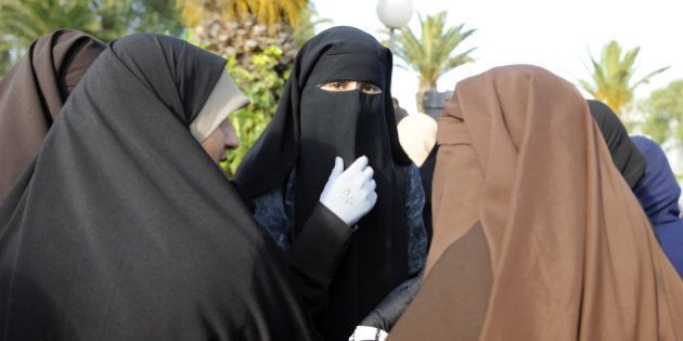 Female students, wearing a niqab, gather outside the building housing the office of the dean of the Faculty...