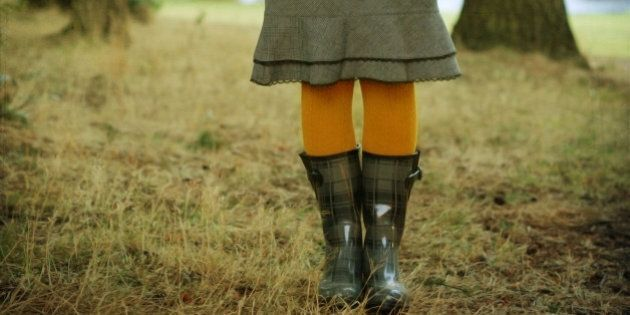 Woman wearing gray rainboots and yellow tights in forest