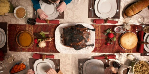 Family observing burnt turkey on dining room