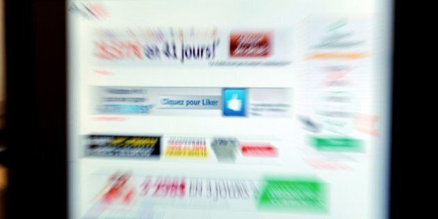Picture taken at the AMF office in Paris on June 20, 2014 shows advertising Internet sites of Foreign...