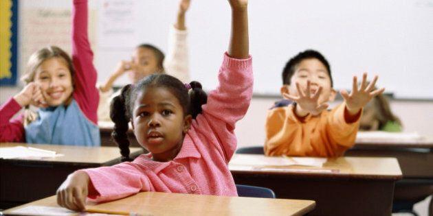 School children raising their hands in