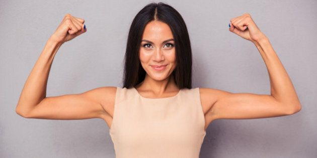 Portrait of a happy elegant woman showing her biceps on gray