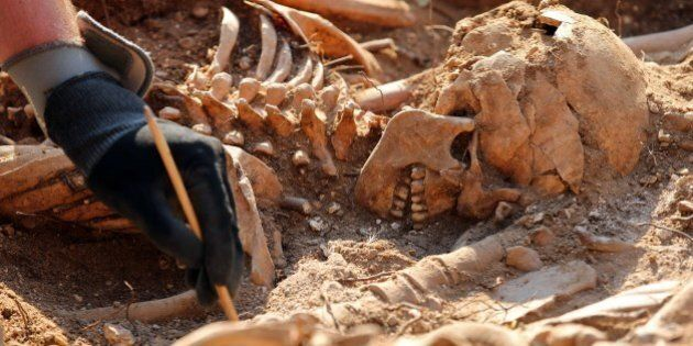 An employee exhumes on Mount Estepar near Burgos on July 24, 2014, the remains of people dumped in mass...