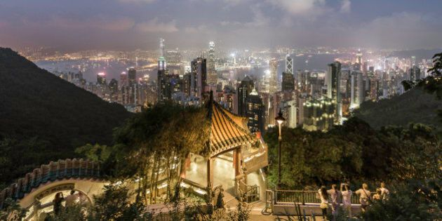 China,Hong Kong, tourists admiring the skyline from Victoria peak, at dusk, standing next to a viewing...