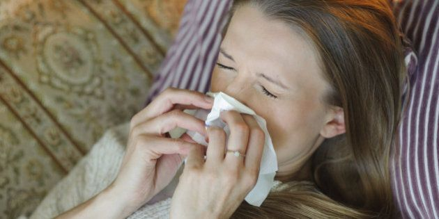 Cold flu illness of woman - tissue blowing runny nose at home