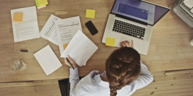 High angle view of an young brunette working at her office desk with documents and laptop. Businesswoman...