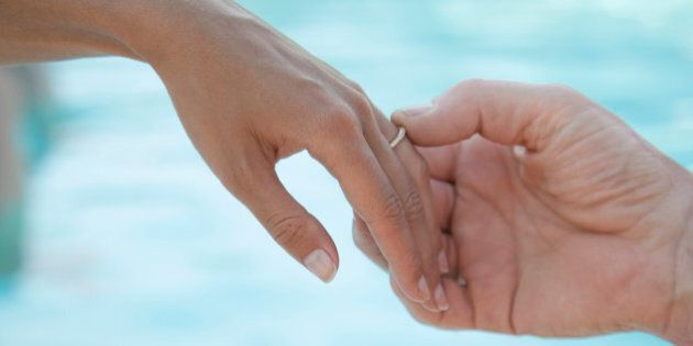 male hand tenderly touching bride's wedding band