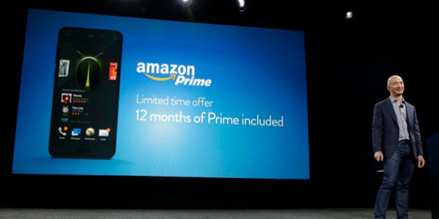 Amazon CEO Jeff Bezos stands next to a graphic that shows that the new Amazon Fire Phone comes with a...