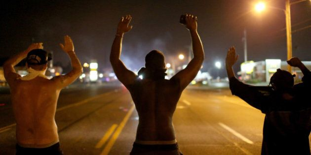 FERGUSON, MO - AUGUST 17: Demonstrators raise their arms and chant, 'Hands up, Don't Shoot', as police...