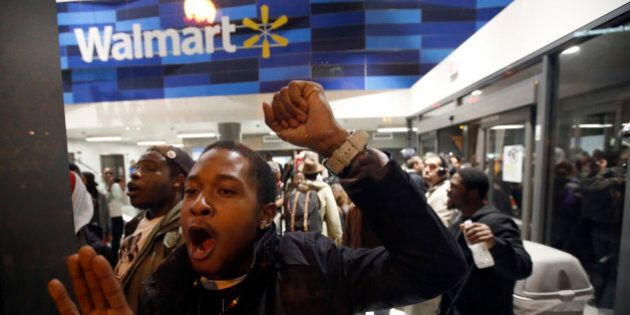 Protestors bang on the glass as they storm a Walmart in Washington, Tuesday, Nov. 25, 2014. A grand jury...