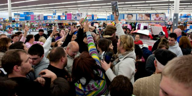 Shoppers vie for copies of video games at a Black Friday sale at a Wal-Mart Stores Inc. store in Mentor,...