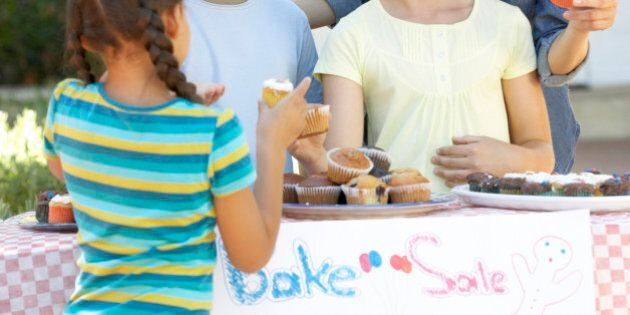 Group Of Children Holding Bake Sale With Mother Smiling And Laughing.
