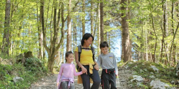 Mother holding her children's hands, walking and chatting happily in the