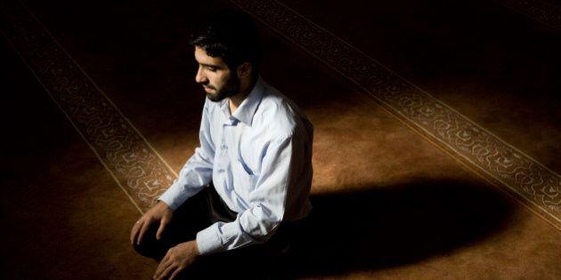 Young muslim man praying in