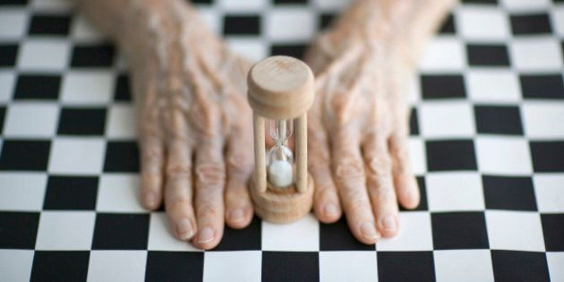 Senior's hands on a checkerboard by an egg-timerTo see my other images about aging please visit
