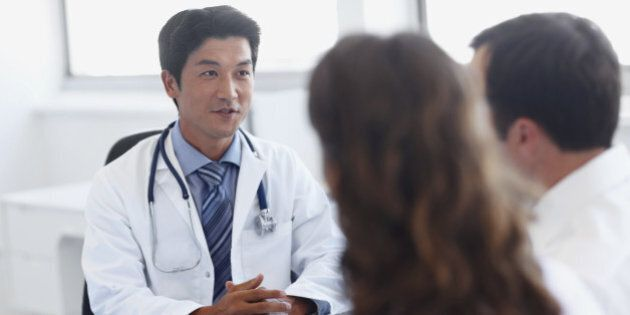 A handsome asian doctor talking with clients in his