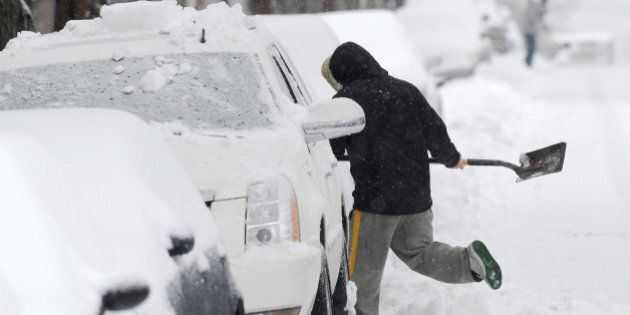 ALEXANDRIA, VA - FEBRUARY 13: Rustin Pierce shovels snow along Queen St. as a snow storm blows through...