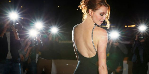 Celebrity in black dress being photographed by paparazzi