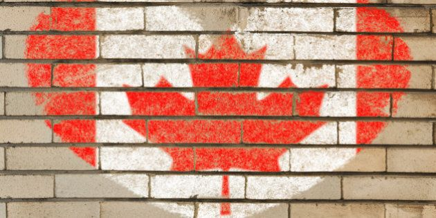 heart shaped flag in colors of Canada on brick