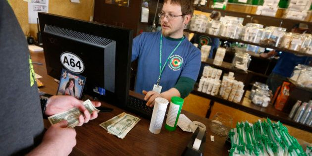 FILE - In this May 8, 2014 file photo, a customer pays cash for retail marijuana at 3D Cannabis Center,...