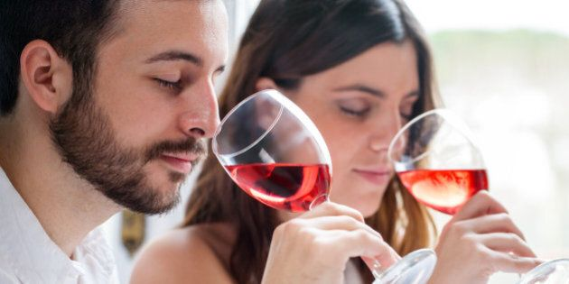 Close up portrait of young couple at wine tasting. Man and woman smelling wine with eyes