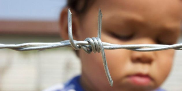 Sad Asian boy behind barbed wire. Focus on barbed wire. Like a refugee