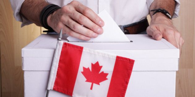 A man casting his vote. The Canadian flag is in front of the ballot box
