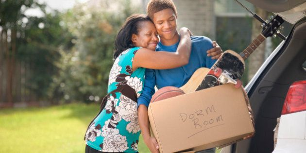 Mother hugging teenage son as he packs for