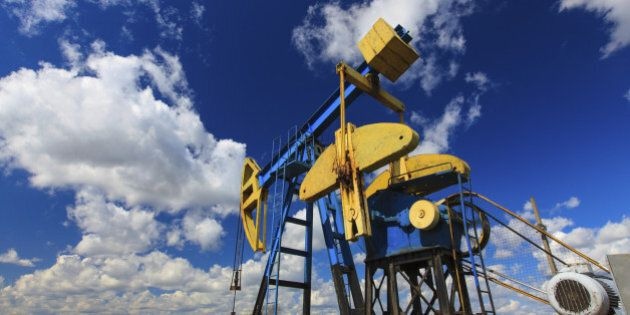 Operating oil and gas well profiled on bright sky with clouds in active European
