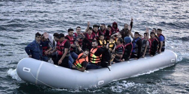 Syrian refugees flash the victory sign as they sit aboard a dinghy carrying heading to the island of...