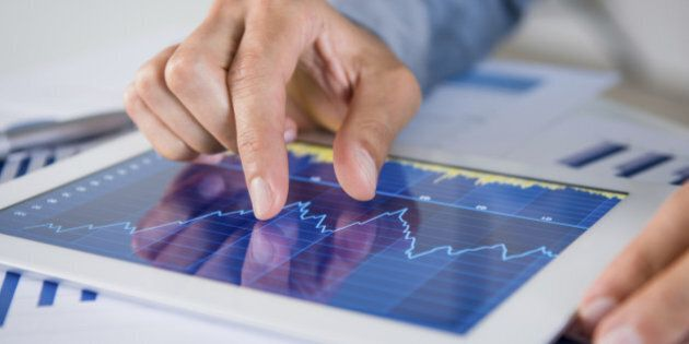 Close Up Of Businessman's Hand Analysing Graph On Digital Tablet