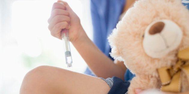 Boy taking insulin injection in leg