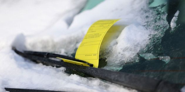 TORONTO, ON - JANUARY 28: A mini van has a snowy windshield and a City of Toronto ticket to go along...