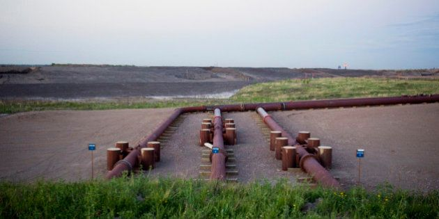 A pipeline leading to the Syncrude Canada Ltd. upgrader plant stands at the company's mine near Fort...