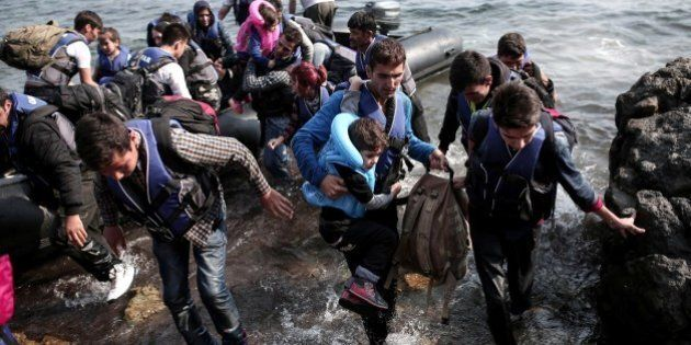 Syrian refugees land on the shores of the Greek island Lesbos in an inflatable dingy across the Aegean...