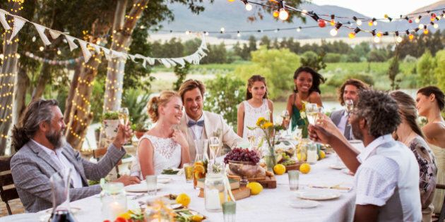 Young couple and their guests sitting at table during wedding reception in